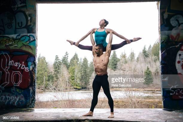 couple practising acroyoga on outdoor stage - split acrobatiek stockfoto's en -beelden