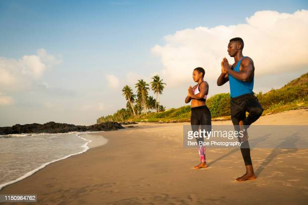 couple practising yoga on beach - ghana independence stock pictures, royalty-free photos & images