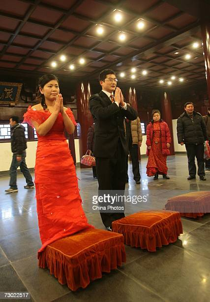A couple pray in front of Buddhist statues during the 'Happiness Express' Collective Wedding Ceremony at the Pilu Temple on January 17 2007 in...