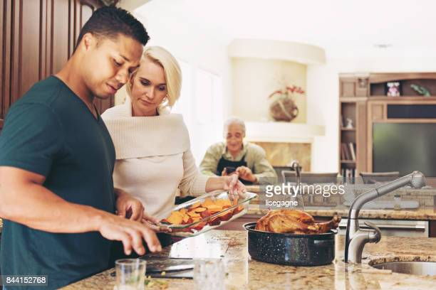 couple prepararing thanksgiving dinner - happy thanksgiving text stock pictures, royalty-free photos & images