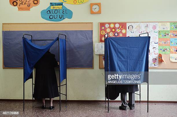 A couple prepare their votes in voting booth at a polling station in Athens on January 2015 Greece votes today in a crucial general election that...