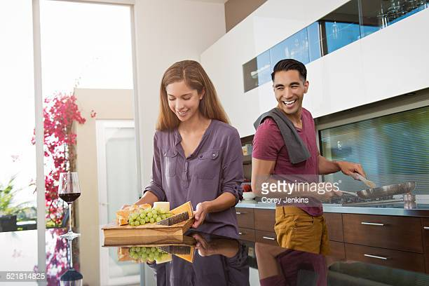 Couple preparing cheeseboard and cooking in kitchen