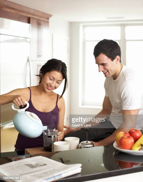 Couple preparing coffee in kitchen