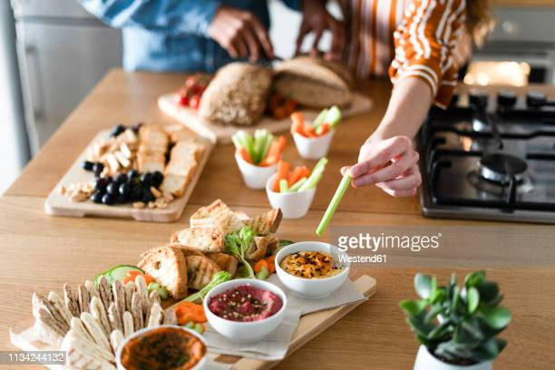 couple preparing dinner party, hand garnishing dips - appetizer stock pictures, royalty-free photos & images