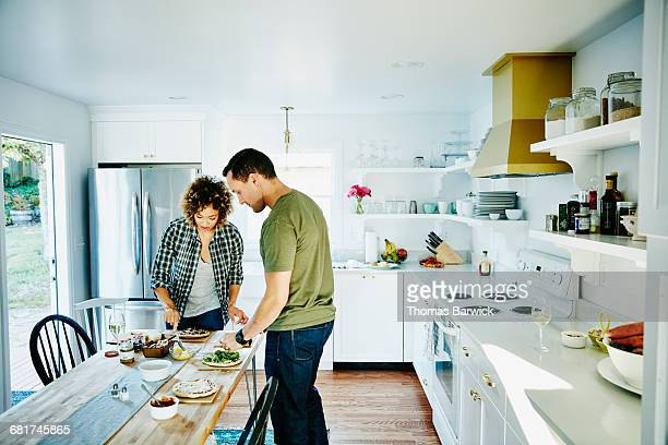Couple preparing family meal together in kitchen