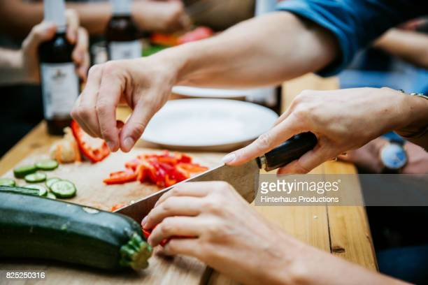 couple preparing food together at barbecue with friends - cutting stock pictures, royalty-free photos & images