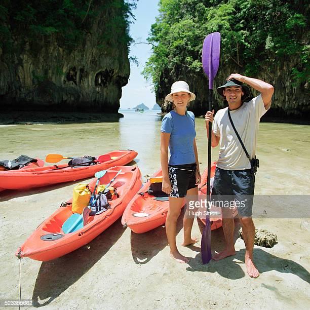 couple preparing for kayak ride, thailand - hugh sitton stockfoto's en -beelden