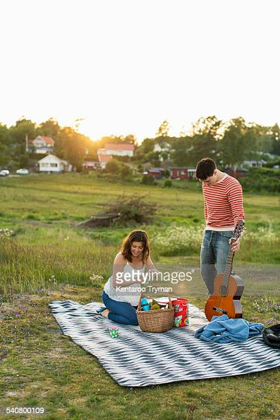Couple preparing for picnic on field