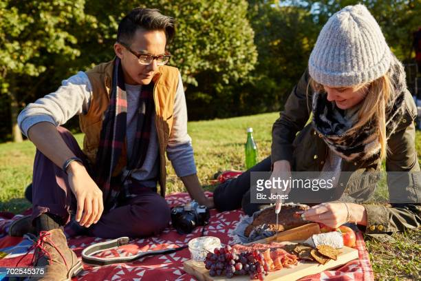 Couple preparing fresh picnic food on cutting board in park