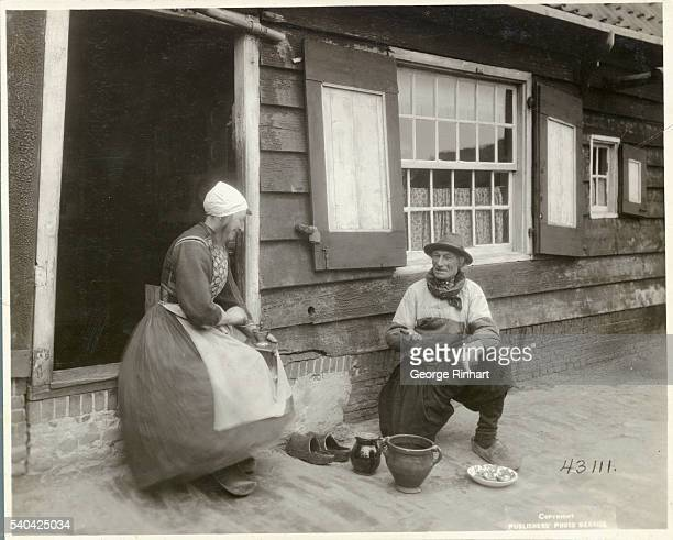Couple Preparing Meal Outside Cottage