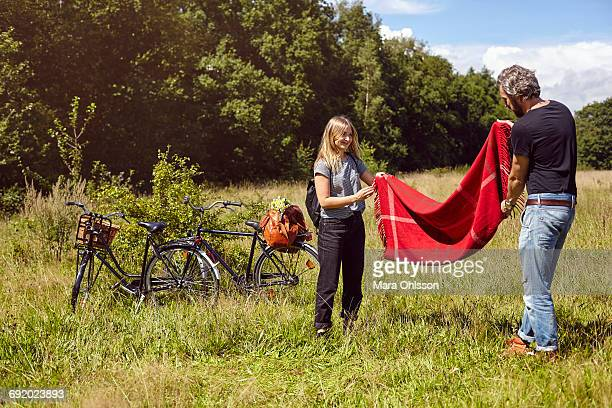 Couple preparing picnic blanket in rural field