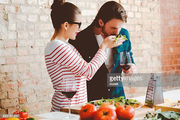 Couple preparing pizza in the modern kitchen, drinking wine