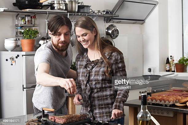 Couple preparing steak in kitchen