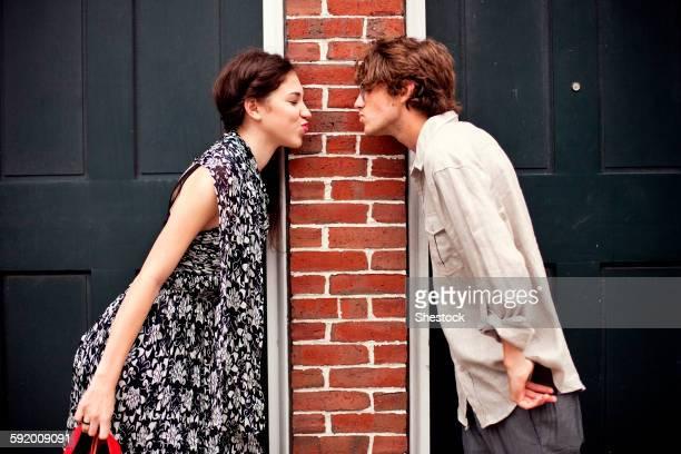 Couple puckering in doorways
