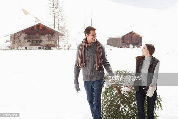couple pulling christmas tree in woods - dragging stock pictures, royalty-free photos & images