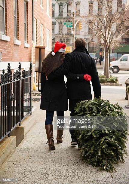 Couple pulling Christmas tree on urban sidewalk