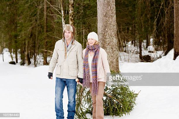 Couple pulling Christmas tree through snow