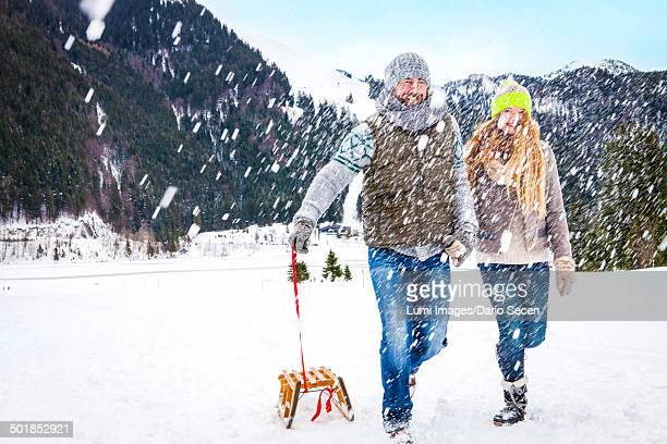 Couple Pulling Sled in Snow, Spitzingsee, Bavaria, Germany