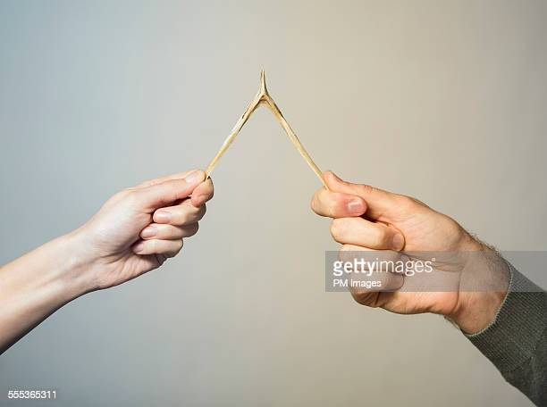 Couple pulling wish bone, close up