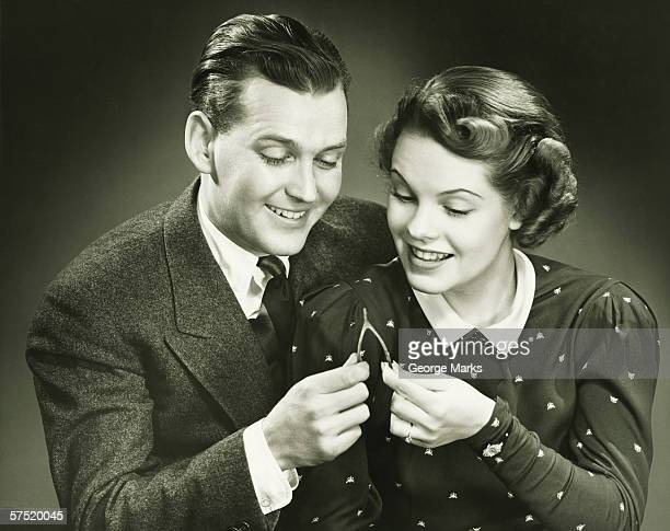 couple pulling wishbone in studio, (b&w), close-up, portrait - luck stock pictures, royalty-free photos & images