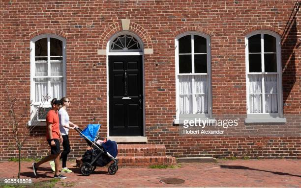 Couple push their child in a stroller along a sidewalk in the Old Town section of Alexandria, Virginia.