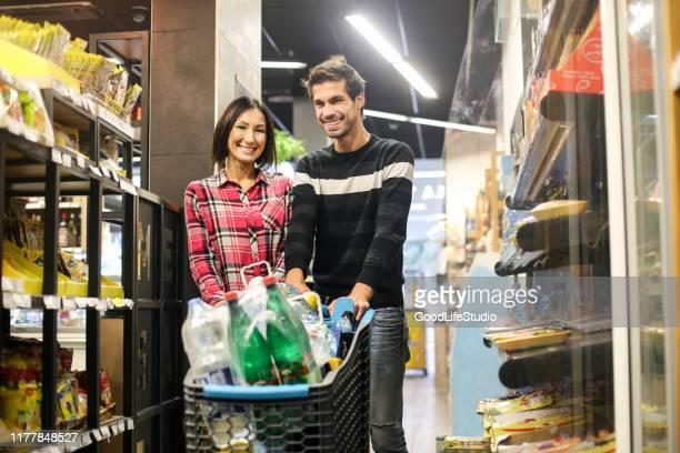couples poussant un chariot dans un supermarché - caddie rempli photos et images de collection
