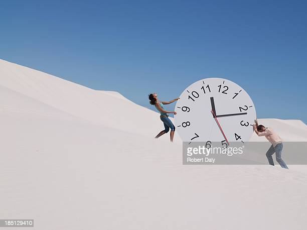A couple pushing a clock in the desert