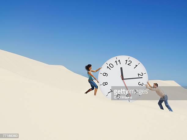 Una coppia, spingendo un orologio nel deserto