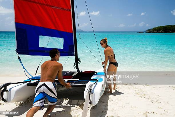 couple pushing catamaran into water to go sailing - catamaran sailing stock photos and pictures