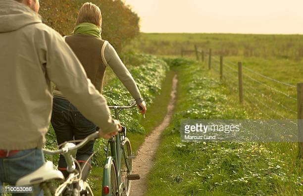 couple pushing old bicycles rear view - suffolk england stock photos and pictures