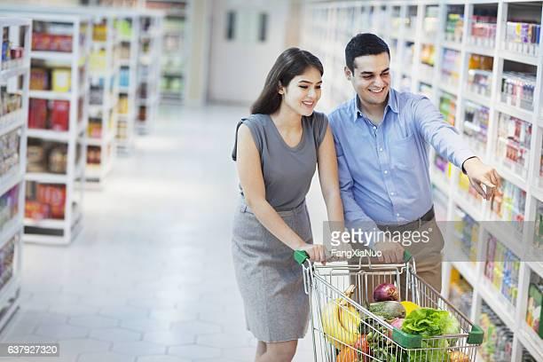 Couple pushing shopping cart in supermarket aisle