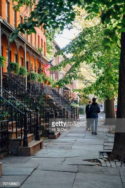 Couple pushing stroller on city sidewalk