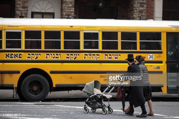 A couple pushing strollers walk past the Yeshiva Kehilath Yakov School in the South Williamsburg neighborhood April 9 2019 in the Brooklyn borough of...