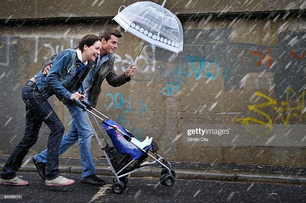 Couple pusing a pram in the rain : Stock-Foto