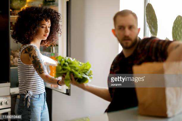couple putting groceries in the fridge - leaf lettuce stock pictures, royalty-free photos & images
