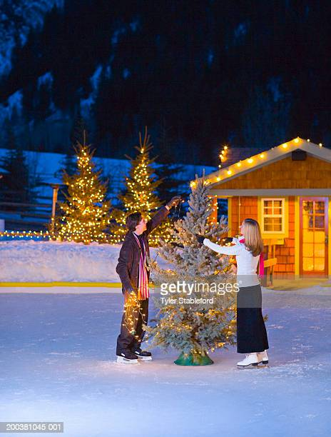 Couple putting lights on christmas tree, skating on ice rink