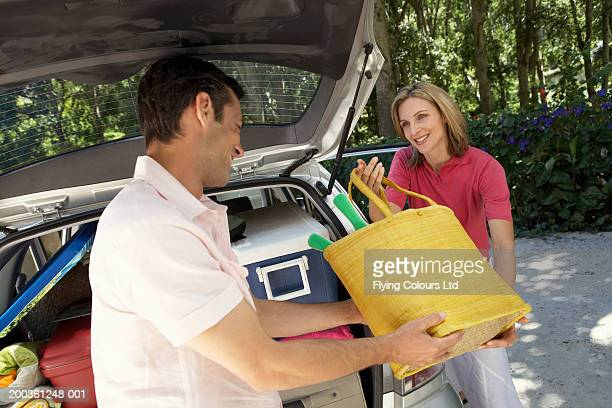 Couple putting luggage in to boot of car, smiling