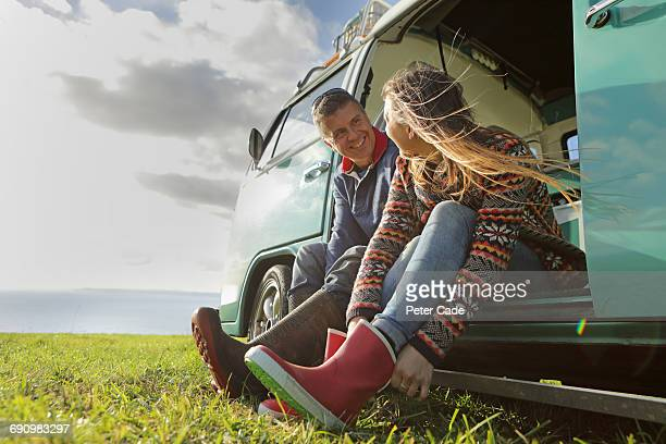 couple putting on wellies sat in door of camper - cornwall england stock pictures, royalty-free photos & images