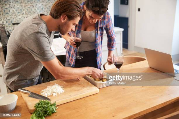 Couple putting potatoes in roasting dish at kitchen table