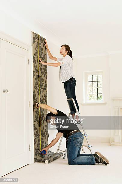 a couple putting up wallpaper - step ladder stock photos and pictures