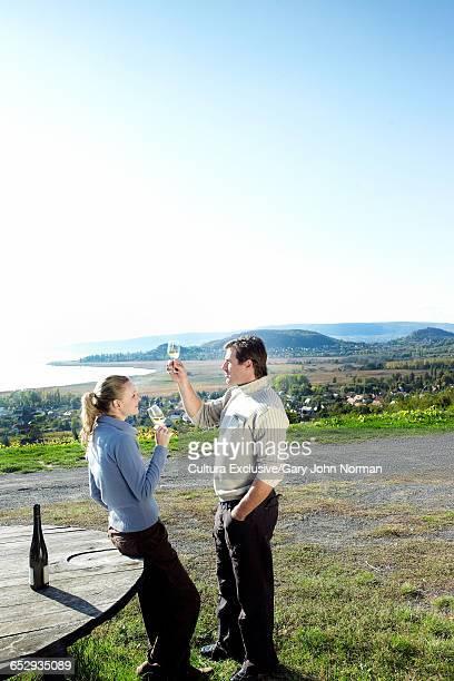 Couple raising a glass at vineyard wine tasting, Lake Balaton, Budapest, Hungary