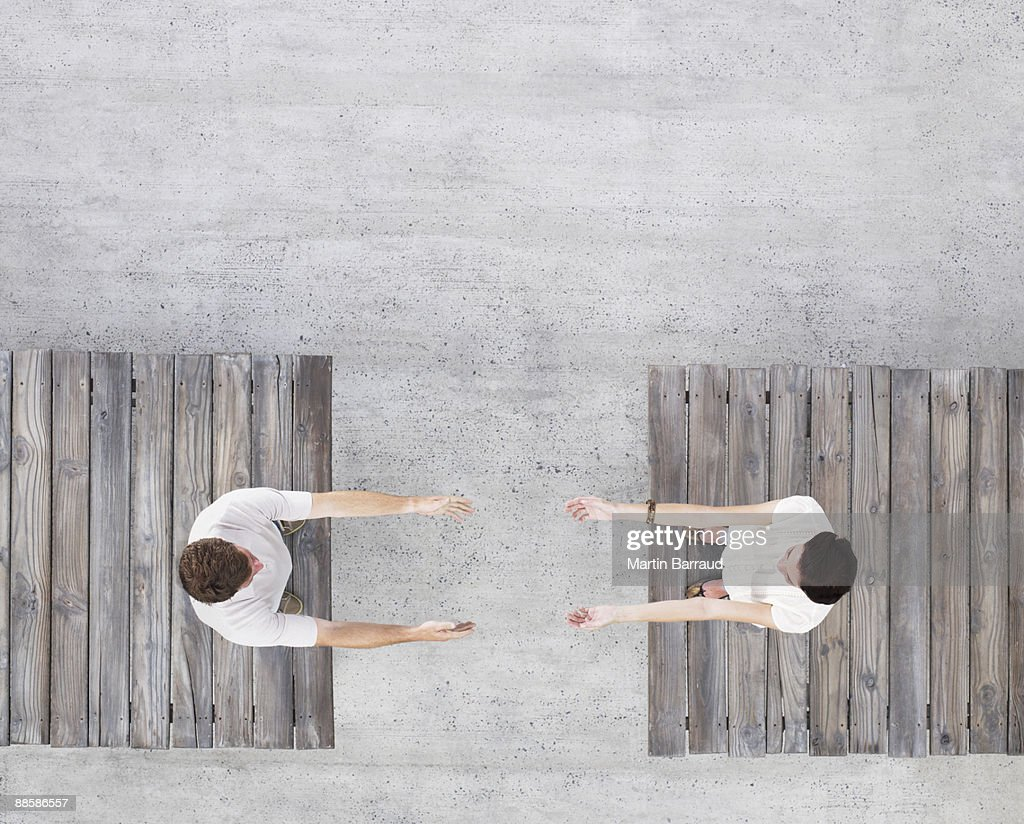 Couple reaching across gap : Stock Photo