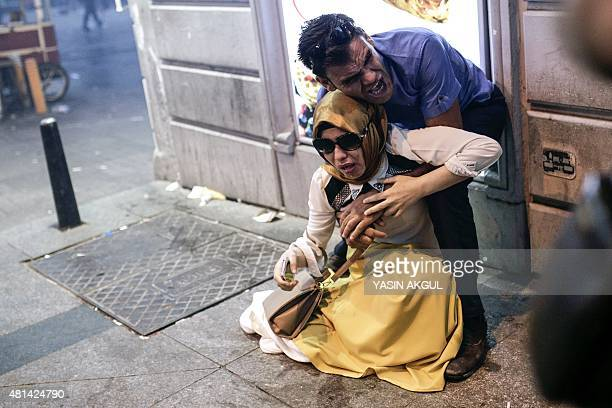 A couple react after being hit with tear gas during a demonstration on July 20 2015 in Istiklal avenue in Istanbul after a suicide bombing in the...