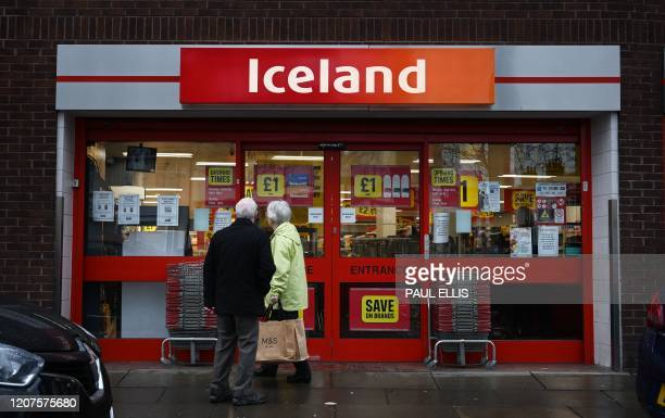 A couple read a notice stating new opening times for an Iceland supermarket in Liverpool north west England on March 18 2020 Many supermarkets are...