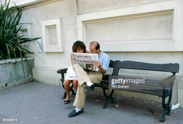 A couple read about the funeral of Princess Grace wife of Prince Rainier of Monaco in a daily newspaper September 18 1982 in Monte Carlo Monaco
