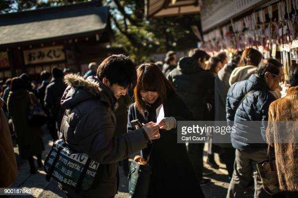 A couple read their 'omikuji' fortunetelling paper strips after praying for the new year at Tsurugaoka Hachimangu Shinto shrine on January 1 2018 in...