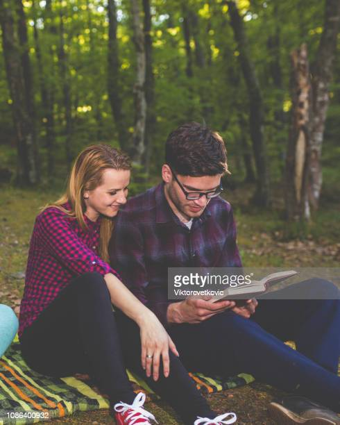 couple reading a book on a picnic - free bible image stock pictures, royalty-free photos & images
