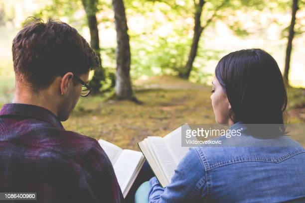 couple reading a book on a picnic - bible photos stock pictures, royalty-free photos & images