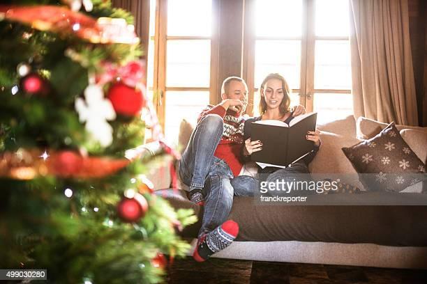 Paar lesen ein Buch über Weihnachten im Wohnzimmer