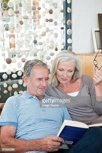 couple reading a book - 65 69 jaar stockfoto's en -beelden